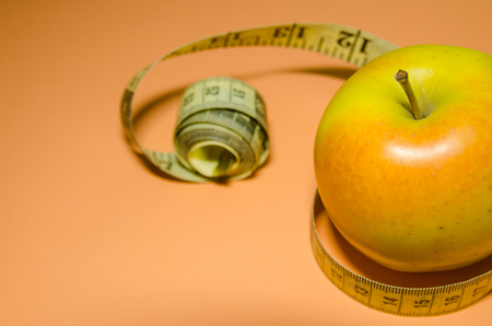 an apple tied with yellow measuring tape concept on orange background. Diet plan and healthy food background.