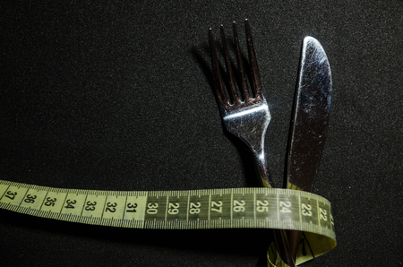 a fork and a knife are tied with yellow measuring tape on black background. Diet and nutrition plan concept. Do not eat unhealthy food from top view with copy space.