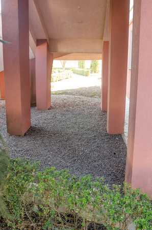 short pink pillars from the building. under the stairs outside