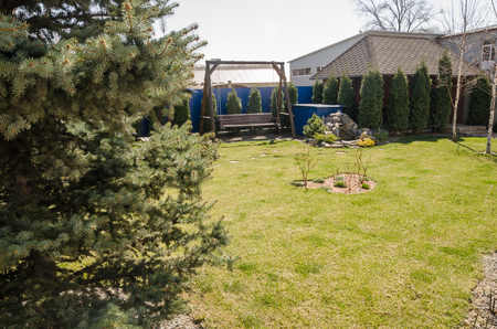 view from the back yard at home at summer season. Landscape design works. Green plants, fir trees and stones in blooming garden. Wooden swings