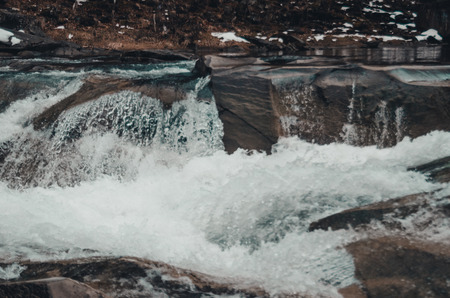 fiume in montagna con vorticoso flusso d'acqua. Grandi massi sullo sfondo del torrente di montagna. Piccola cascata da vicino. Bukovel, Ucraina nella stagione invernale Archivio Fotografico