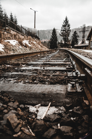 rails in the winter morning while the snow is melting concept. Trees and mountain are on the background. Empty railroad track.