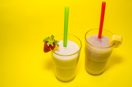 milkshakes in glass cups with straws on yellow background. Vanilla and chocolate milkshakes with banana and strawberry