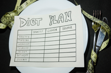 black background of blank nutrition plan with copy space and measuring tape. Diet food and loosing weight control concept.
