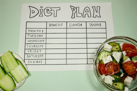background of blank nutrition plan with copy space, red dumbbell and organic salad. Diet food and loosing weight control concept. Puffed rice bread sandwich.