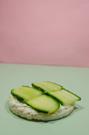 background of puffed rice bread with sliced cucumbers and cream cheese. Organic sandwich with copy space. Diet food conept.