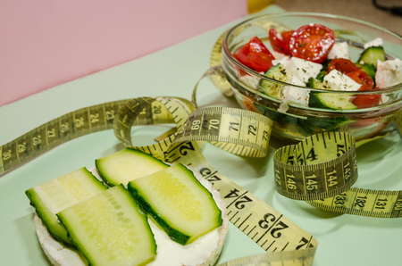 background of organic salad of tomatoes and cucumbers with a measuring tape and puffed rice breads. Diet and loosing weight concept. Reklamní fotografie
