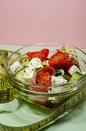 background of organic salad of tomatoes and cucumbers with a measuring tape. Diet and loosing weight concept.