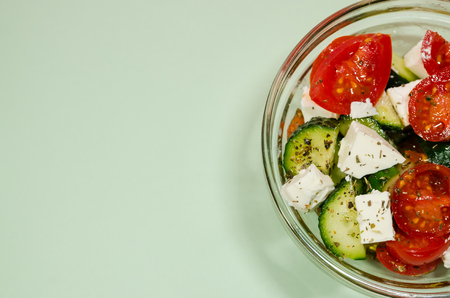Blue background of organic salad of tomatoes and cucumbers in glass bowl with copy space. Healthy lifestyle concept. Reklamní fotografie