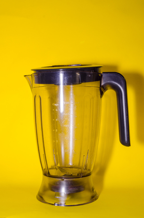 empty glass blender with a cover on yellow background