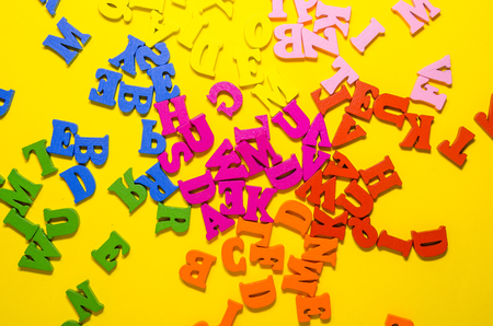 the mess of colored alphabetic letters on yellow background from top view