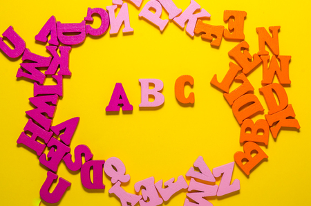 colored a b c with wooden letters in the circle. learn beginning of alphabet concept