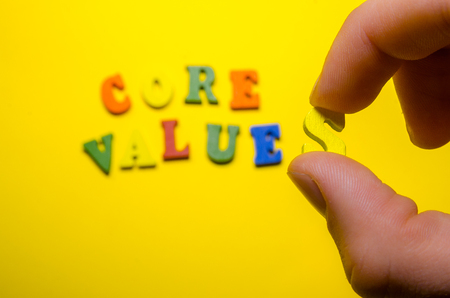 words core values with wooden letters. a hand holding one letter Reklamní fotografie