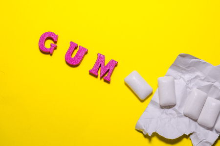 word gum compossed with wooden pink letters. white pads of chewing gum Reklamní fotografie