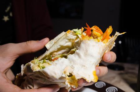 hands holding a half of shawarma with ingedients inside on black background. eating kebab concept Reklamní fotografie