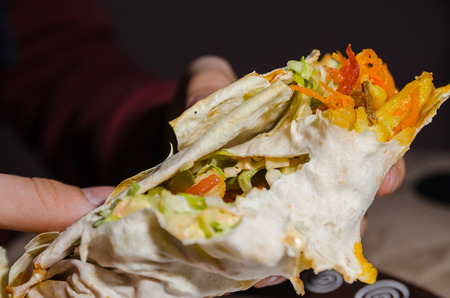 hands holding a half of shawarma with ingedients inside on black background. eating homemade fresh kebab concept