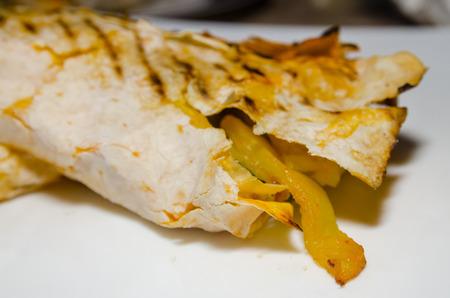Fresh thin lavash or pita bread roll of shawarma sandwich with ingredients inside.