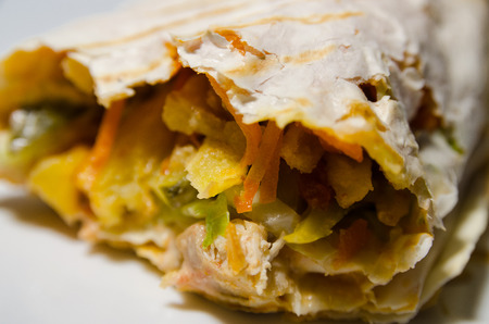 Fresh thin lavash or pita bread roll of shawarma sandwich with ingredients inside on white plate.