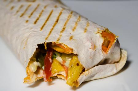 bitten shawarma with chicken on white plate Reklamní fotografie