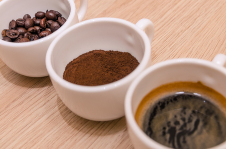 difference stages of coffee preparation - ground, grain, beverage in three cups on the table. Reklamní fotografie
