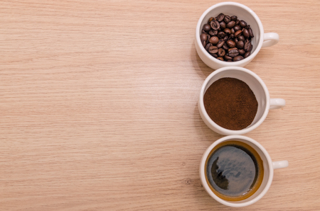 difference stages of coffee preparation - ground, grain, beverage in three cups on the wooden table with copy space.