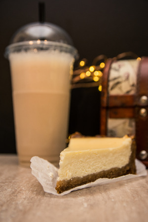 a slice of cheesecake is on focus. vanilla milkshake in the plastic cup is on the black background
