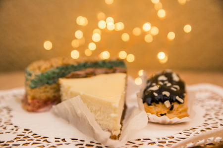 different desserts on the wooden table with bokeh lights background. A slice of sheesecake, chocolate eclair and waffle cake for menu in coffee shop