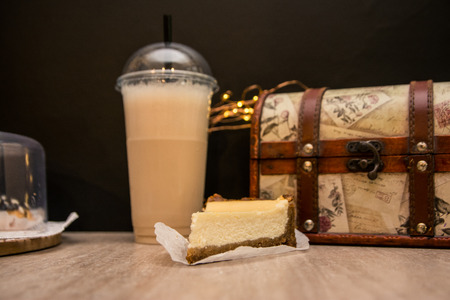 a slice of cheesecake and vanilla milkshake in the plastic cup are on the table. wooden box as decor for coffee shop