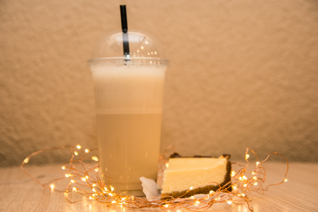 a slice of cheesecake and vanilla milkshake in takeaway cup on wooden table served in coffee shop Reklamní fotografie