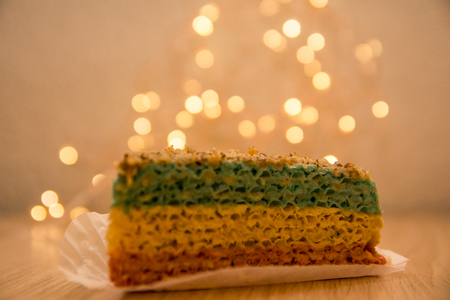 a piece of colored waffle cake with  condensed milk inside close up view. bokeh lights background in the coffee shop Reklamní fotografie