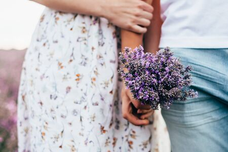 a young love couple with a bunch of lavender flowers in the field
