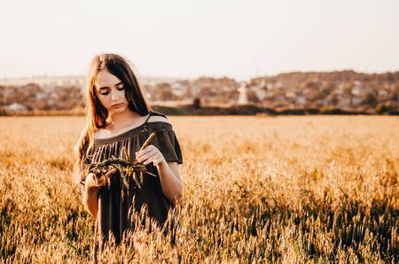 woman in dress making a wreath for head in wheat field