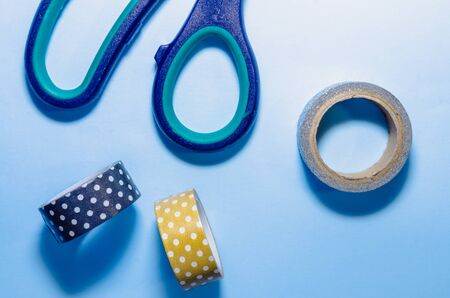 colorful washi tapes with scissors isolated on blue background from top view