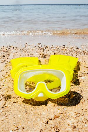 yellow swimming mask with flippers on sand beach by the sea