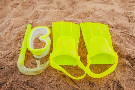 yellow swimming flippers with mask and tube on sand beach 写真素材