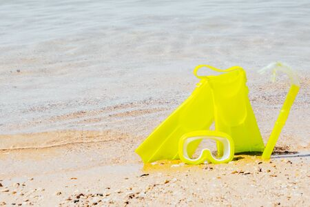 yellow swimming flippers with mask and tube on sand beach by the clear sea
