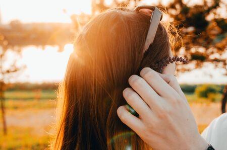 Joven pone una flor detrás de la oreja de su novia al aire libre mientras se pone el sol