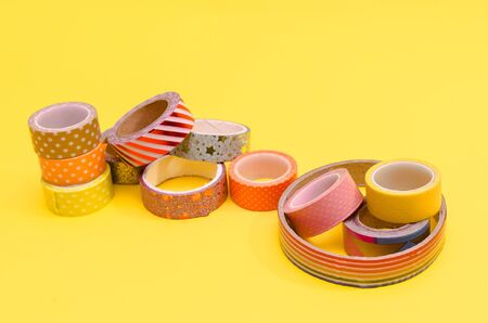 colorful washi tapes isolated on yellow background from top view Banco de Imagens