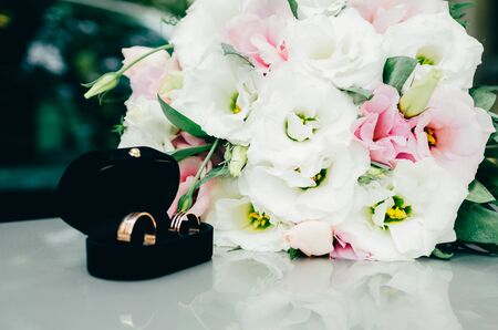 wedding rings in opened black box with bride bouquet on the background 写真素材