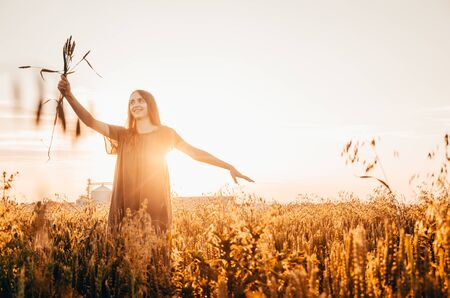 happy woman in green dress stands smilling in wheat field with shining sun