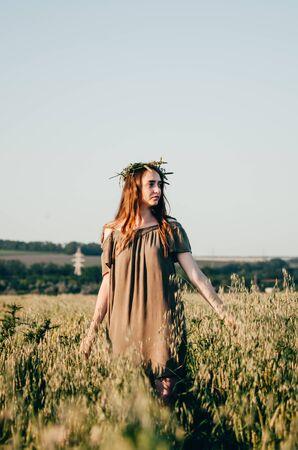 woman in green dress walks on path in wheat field in countryside