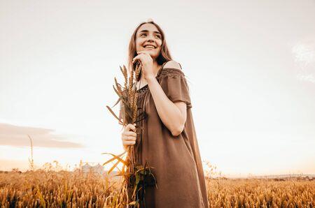 happy woman in green dress standing in wheat field