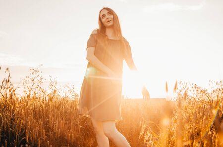 woman in green dress standing in wheat field with shining sun