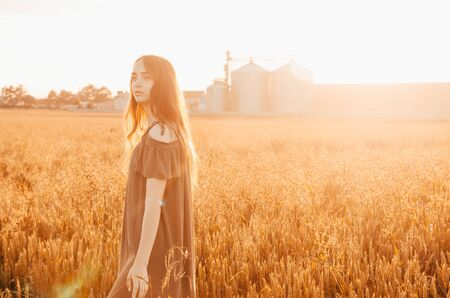 woman in green dress standing in wheat field with shining sun Banque d'images