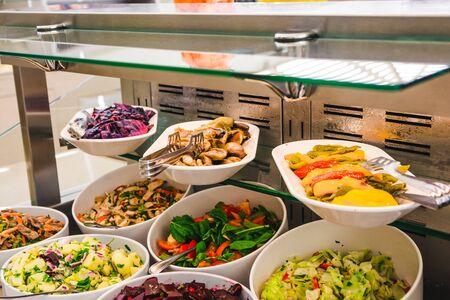 stół bufetowy z sałatkami i warzywami w dużych białych talerzach.