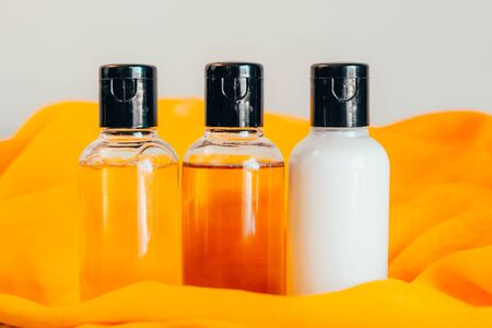 close up view of shower gel, shampoo and body lotion in small travel tubes in hotel bathroom on orange towel