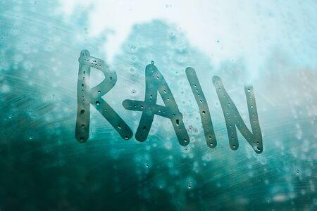 word rain written on foggy window in rainy weather outdoors