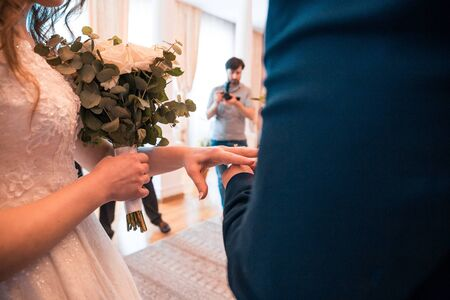 Groom slipping ring on finger of his bride at wedding day