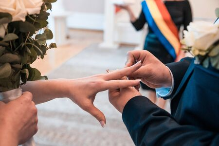 Groom is putting on a ring on finger of his bride at wedding