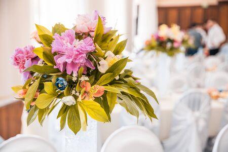 ein Blumenstrauß in einer Vase auf gedeckten Tischen bei der Hochzeit. Bankettkonzept Standard-Bild